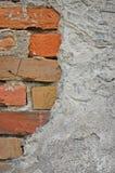 För stenvägg för röda tegelstenar closeup för bakgrund, sprucken förstörd stuckatur arkivfoto