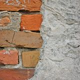 För stenväggen för röda tegelstenar closeupen för bakgrund, den spruckna förstörda stuckaturen, lodlinje rappad grå beiga för gru royaltyfri foto