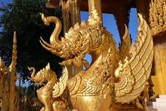 För stillejon för unik design en guld- typisk thailändsk staty står ut från den blåa himlen i central region av Thailand Royaltyfri Fotografi