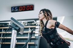 För stimulanskvinnor för EMS electro övningar med lagledaren i modern idrottshall royaltyfri fotografi