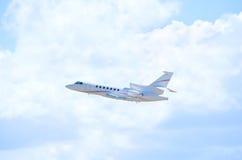För stråltrafikflygplan för privat affär nivå i flykten mot fluffiga moln arkivfoto