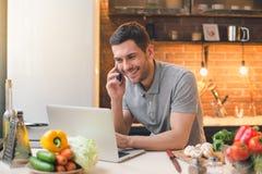 För strikt vegetarianmål för ung man förberedelse genom att använda bärbara datorn royaltyfri foto