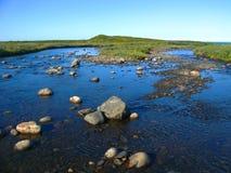 För suddigt grund flod siktslandskap för bakgrund som flödar över platån och flödar in i det Barents havet Royaltyfri Fotografi