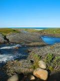 För suddigt grund flod siktslandskap för bakgrund som flödar över platån och flödar in i det Barents havet Arkivfoto