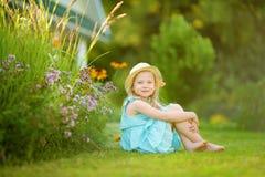 För sugrörhatt för gullig liten flicka bärande sammanträde på gräset på solig sommardag Barn och blommor, sommar, natur och gycke arkivbild