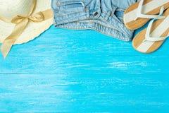 För sugrörhatt för ram elegant kvinnlig jeans för häftklammermatare på blå träbakgrund, copyspace för text, sommarsemester arkivbild