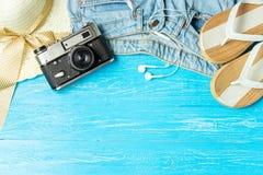 För sugrörhatt för ram elegant kvinnlig kamera för jeans för häftklammermatare på blå träbakgrund, copyspace för text, sommarseme arkivbild