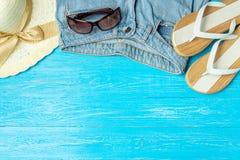 För sugrörhatt för ram elegant kvinnlig solglasögon för jeans för häftklammermatare på blå träbakgrund, copyspace för text, somma royaltyfri fotografi