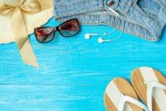 För sugrörhatt för ram elegant kvinnlig solglasögon för jeans för häftklammermatare på blå träbakgrund, copyspace för text, somma fotografering för bildbyråer