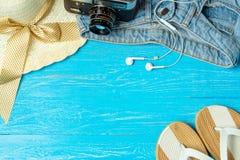 För sugrörhatt för ram elegant kvinnlig solglasögon för jeans för häftklammermatare på blå träbakgrund, copyspace för text, somma arkivbild