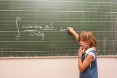 För svår matematikuppgift för en liten skolflicka royaltyfria bilder
