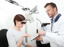 För synförmågakvinna för optometriker undersökande patient i optikerkontor royaltyfri bild