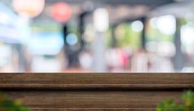För tabellöverkant för tomt moment mörk wood ställning för mat med suddighetskaférestaur royaltyfri foto
