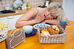 för tabellkvinna för frukost sömnig gäspning arkivbilder