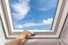 För takfönstermansard för man nära nytt fönster i ett loftrum mot blå himmel Arkivbild