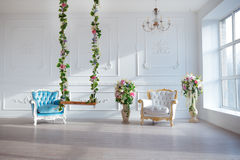 För tappningstil för vitt läder stol i klassiskt inre rum med det stora fönstret och våren blommar royaltyfria foton