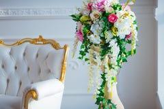 För tappningstil för vitt läder stol i klassiskt inre rum med det stora fönstret och våren blommar royaltyfri fotografi