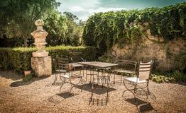 För tappningträdgård för sommar fridsam vrå med metallmöblemang royaltyfri fotografi