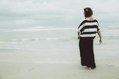För tatueringhipster för stående ensam ställning för asiatiska enkla indy kvinnor bara på stranden royaltyfri bild