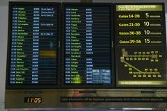 För tecken en Heathrow in flygplats i England för avgå och ankomstflygtider och flygbolagportar Arkivfoto