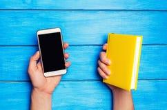 För telefon bok kontra En man rymmer en gul bok och en telefon på en blå träbakgrund Valet mellan studien och telefonen telefon Royaltyfria Foton