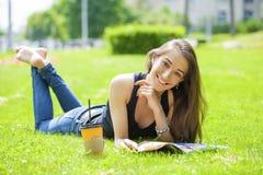 för tidskriftavläsning för gräs liggande barn för kvinna arkivbilder