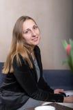 För tidskriftstående för ung kvinna läs- skott för studio Arkivfoton