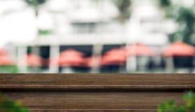 För träöverkant för tomt moment mörk ställning för mat med suddighetsparaplyet på semesterorten Royaltyfri Fotografi