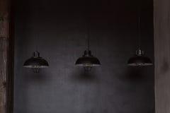 För trådhänge för vind industriella lampor mot den grova väggen Royaltyfri Foto