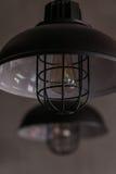 För trådhänge för vind industriella lampor mot den grova väggen Royaltyfri Bild