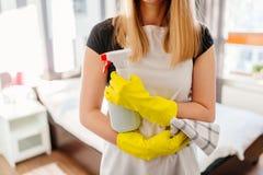 För trasa- och sprejflaska för kvinna hållande tvättmedel Royaltyfri Bild