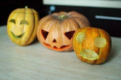 ` För tre stålar-nolla - lyktor från pumpa och melon på köksbordet Arkivbild