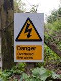 För triangeltecken för varning över huvudet levande trådar för gul fara Royaltyfri Bild