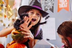 För trollkarlallhelgonaafton för svartögd flicka som bärande dräkt spelar trick arkivfoto