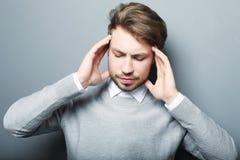 För tryckhuvudvärk för affärsman som stressat bekymmer isoleras på grå färger b royaltyfri bild