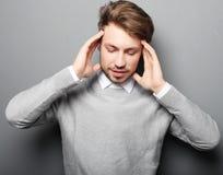 För tryckhuvudvärk för affärsman som stressat bekymmer isoleras på grå färger b royaltyfri fotografi