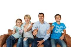 För tummar lycklig familj upp - på en soffa på vit Royaltyfri Fotografi