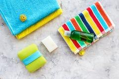 för tvålhandduk för badrum stearinljus isolerad set white Handdukar, flaskor med tvål och schampo på grå färger stenar copyspace  Arkivfoton