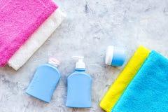 för tvålhandduk för badrum stearinljus isolerad set white Handdukar och flaskor med tvål och schampo på grå färger stenar copyspa Arkivfoton