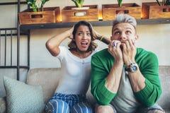 För tvsport för par hållande ögonen på lek för fotboll Arkivfoto