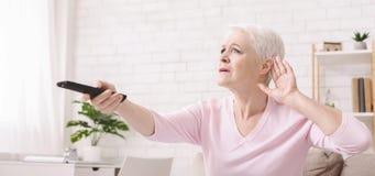F?r tvupps?ttning f?r ?ldre kvinna stigande volym med fj?rrkontroll arkivbild