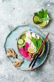För udonnudlar för strikt vegetarian asiatisk bunke för soppa med ingefäran och champinjoner buljong, tofu, plötsliga ärtor, zucc arkivbilder