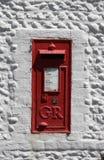 För UK-postbox för tappning röd uppsättning i en vit vägg Arkivbild