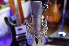 `` För `-Unretouched för allsång III slut för mikrofon för kondensator studio upp med instrument i bakgrunden royaltyfri foto