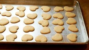 För valentinsocker för farmödrar smakliga hemlagade kakor på bakplåten precis ut ur ugnen