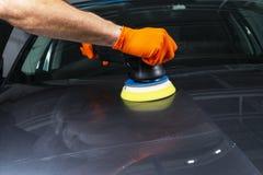 För vaxarbetare för bil som polska händer applicerar det skyddande bandet, innan polering Polerande och polerande bil Specificera royaltyfria foton