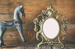 För victorianstil för antikvitet tom ram och gammal vagga häst över trätabellen Arkivfoton