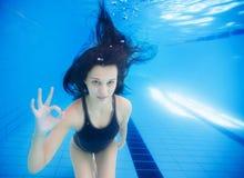 För visningok för ung flicka undervattens- tecken royaltyfri foto