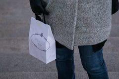 För vitbokshopping för kvinna bärande påse från Prada arkivbild