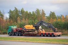 För Volvo för Volvo FH lastbiltransportsträckor grävskopa hydraulisk crawlsimmare royaltyfria bilder